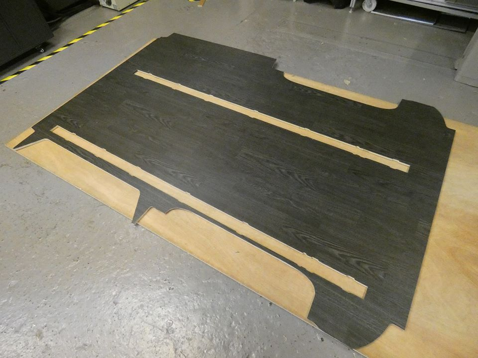One piece floor production including sliding seat rail cutouts